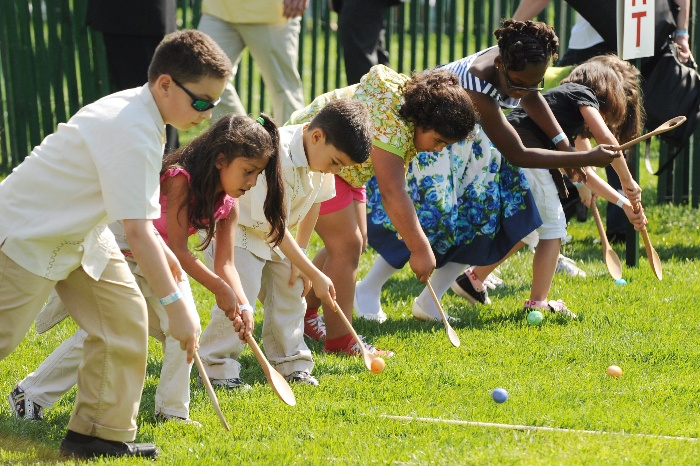 egg roll children with wooden spoons rolling eggs on a green lawn