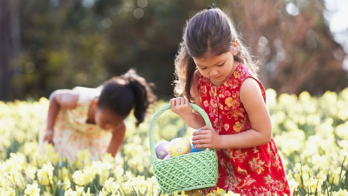 two girls with baskets in a field of flowers searching for easter eggs