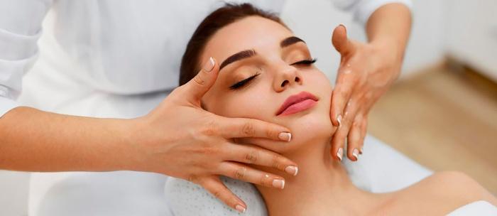 woman getting a facial massage at a salon closing her eyes and enjoying