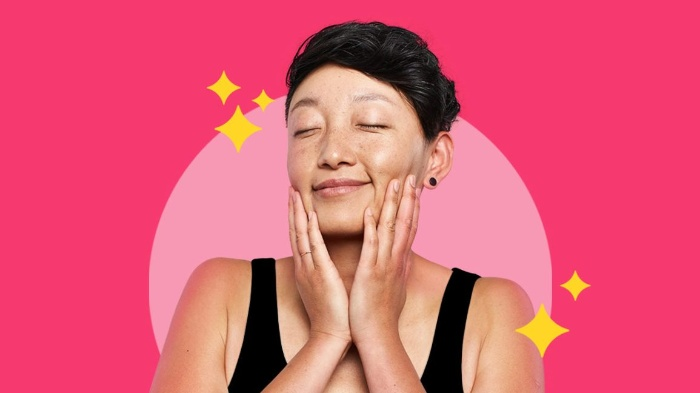 woman with black hair and black top enjoying her healthy and glowing skin on a pink background with her eyes closed