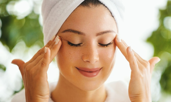 woman with white towel on her head outdoors enjoying a calming facial massage with her eyes closed