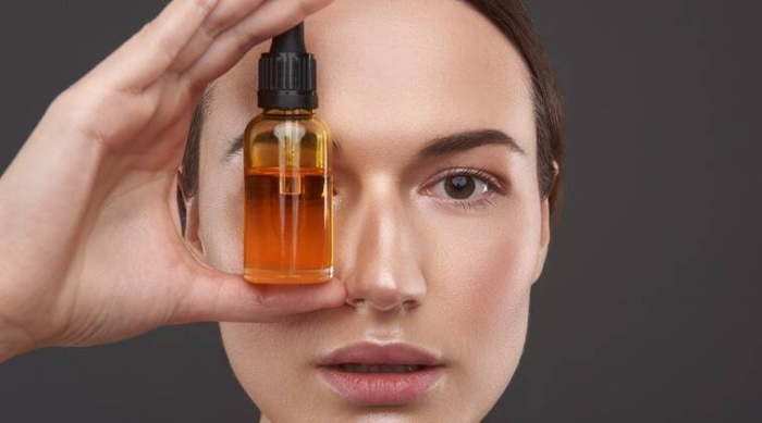 woman holding a light brown small bottle of skin oil in front of her eye