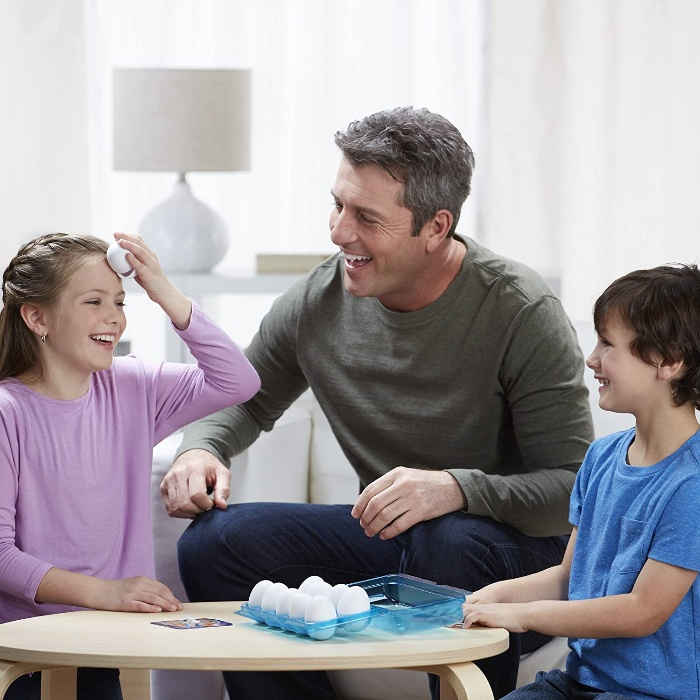 father with two children playing an egg roulette at home
