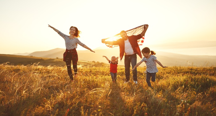 family enjoying time outdoors on a field at sunset