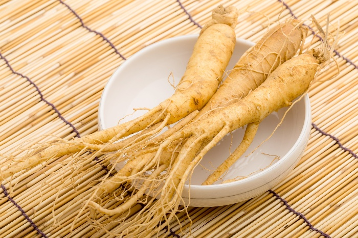 three gingseng roots in a white bowl on a hay table cover