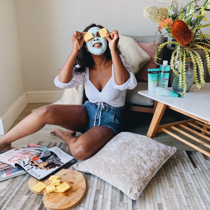 girl skin care girl sitting on the floor with a blue mask on putting pieces of fruit on her eyes