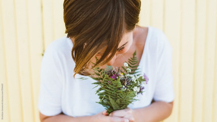 girl in a white dress with short hair holding a wildflower bouquet