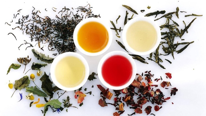 four different herbal teas in different colors and dry herbs around them