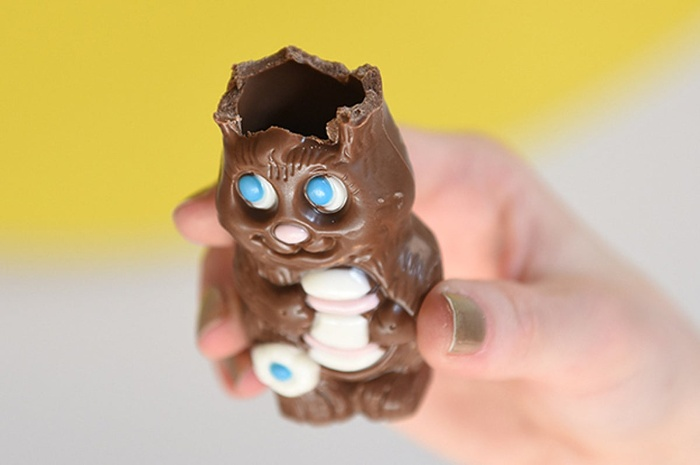 hand holding a hollow easter chocolate bunny missing his ears