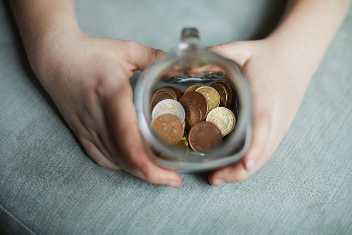 two hands holding a jar full of coins on a grey sofa