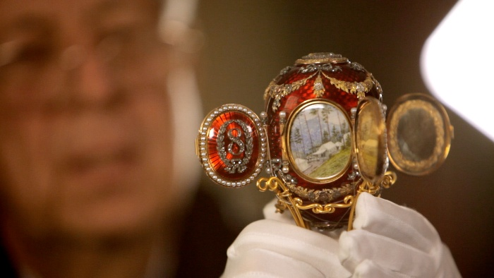 jewel eggs red faberge egg held by a jeweller