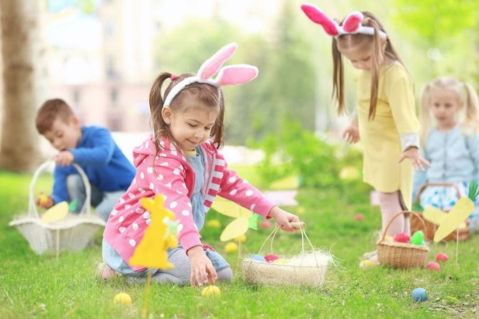 kids dressed like bunnies collecting eggs in baskets