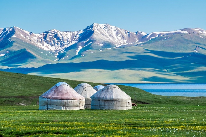 kyrgyzstan landscape with tents mountains green fields and lake