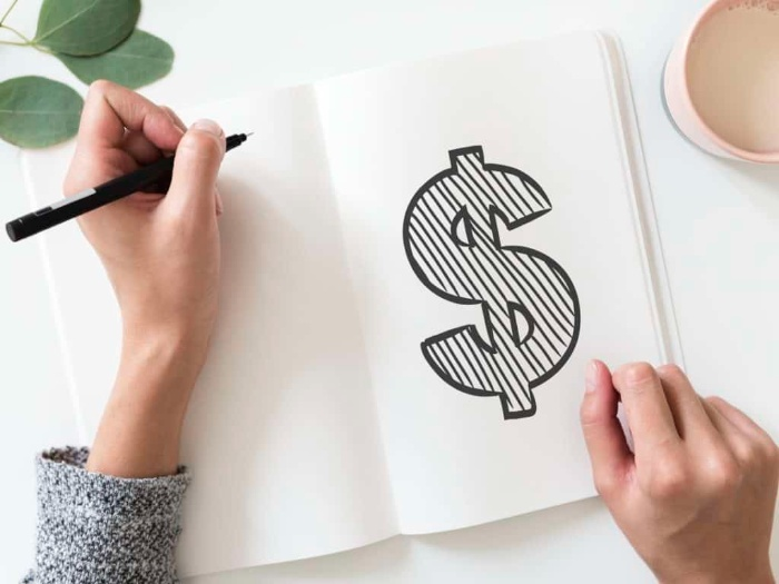 money saving tips woman writing a dollar sign into a white notebook with a black pen