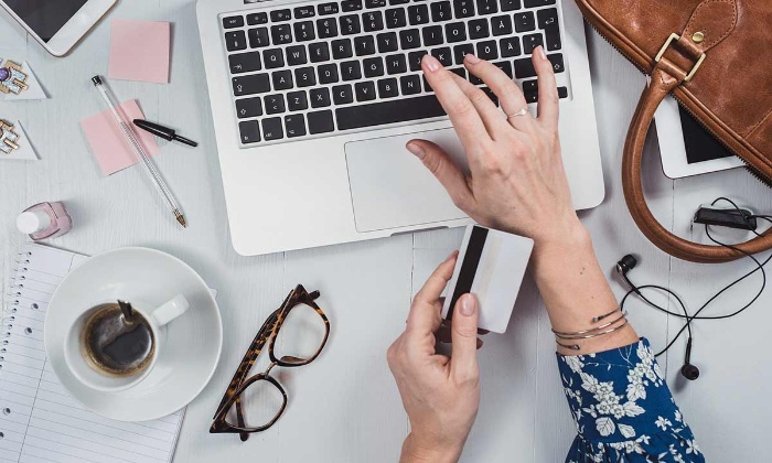 money tips woman with a card in her hand writing on a laptop on her desk with a cup of coffee and glasses