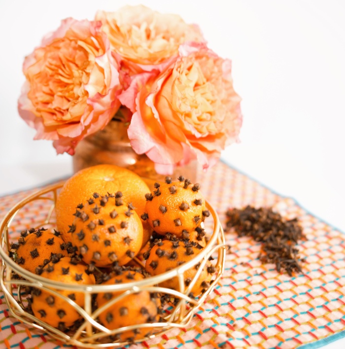 natural aromas oranges and cloves on a table with fresh flowers