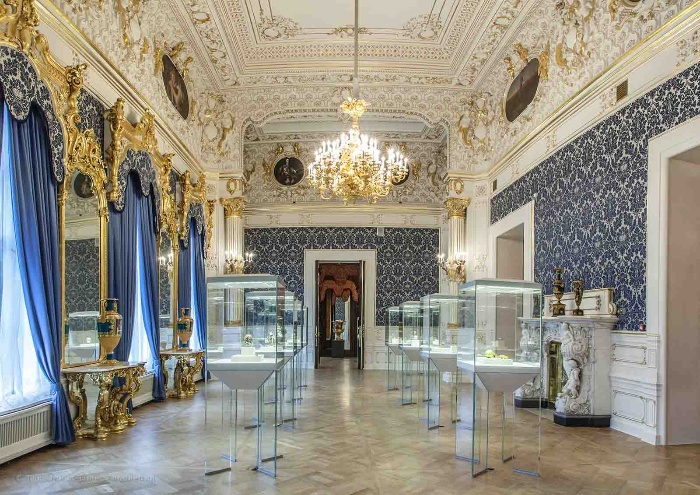 opulent blue room in a palace with a faberge egg display