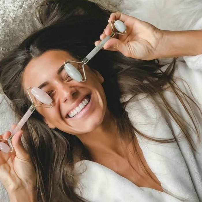 woman lying on her back with two face rollers on her eyes smiling with her eyes closed