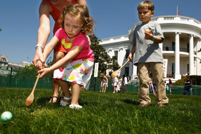 children rolling eggs with wooden spoons in front of the white house