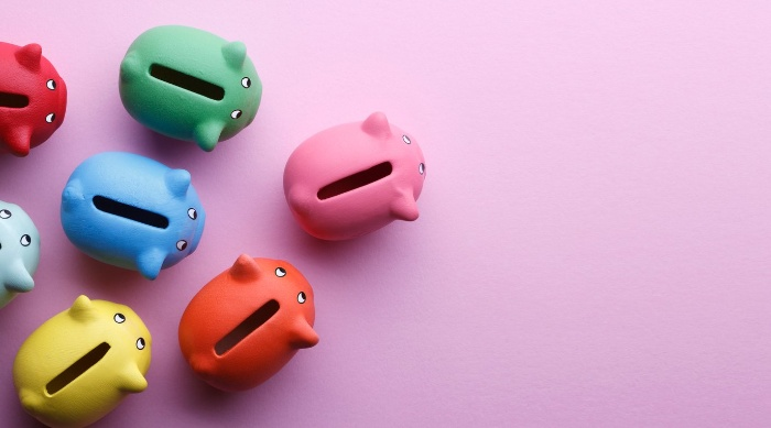 small colorful piggy banks on a pink background