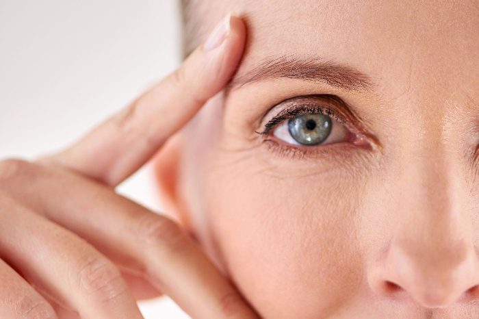 close up woman with blue eye and wrinkles holding her face
