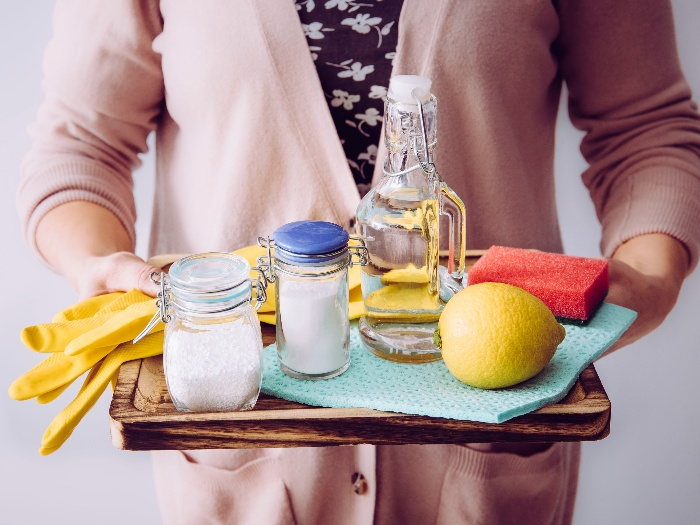 woman in pink cardigan holding a tray with natural cleaning products soda lemon yellow gloves