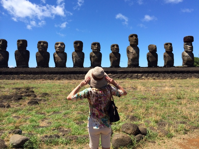 tourism easter islands woman with a sun hat looking at the stone statues