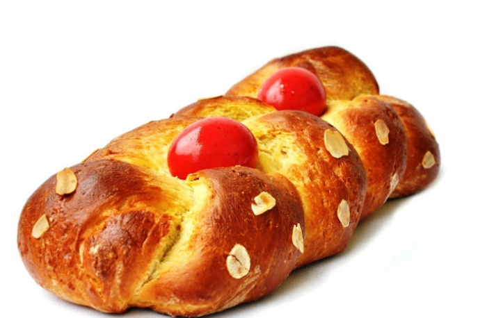 Greek tsoureki bread with red eggs and nuts on top