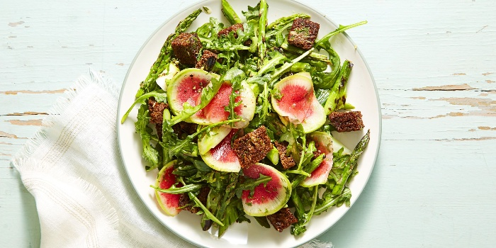 vegan menu green salad with rucola and pieces of fruit on a white table