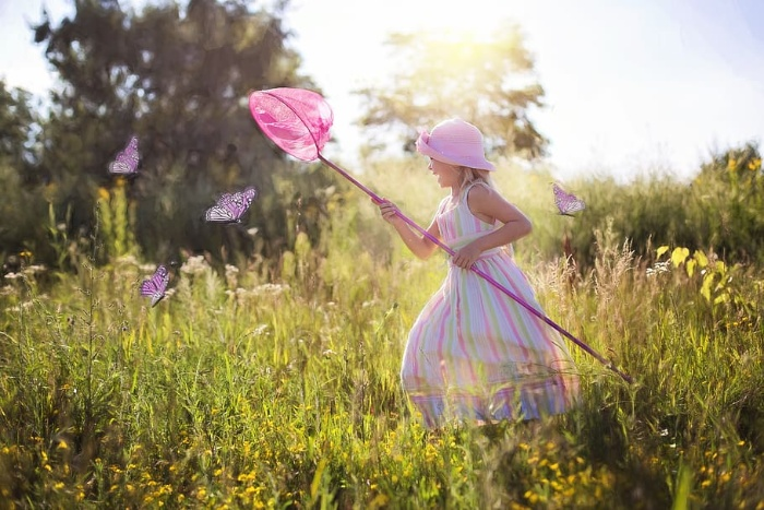 Girl in a summer dress with a pink hat in grass field chasing butterflies