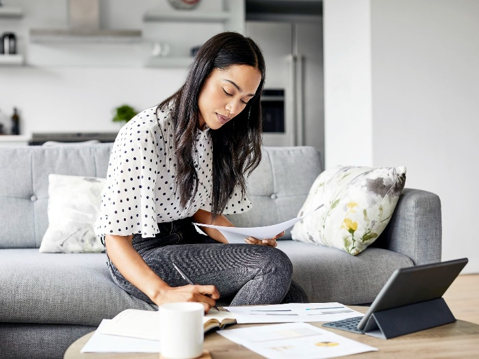 woman bills sitting on the sofa at home calculating bills and writing down