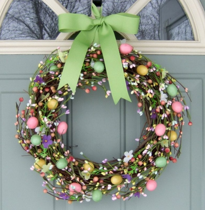 pretty spring wreath with a green ribbon on the outside of a door