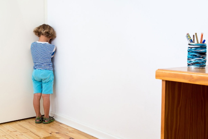 little boy dressed in blue standing in the corner