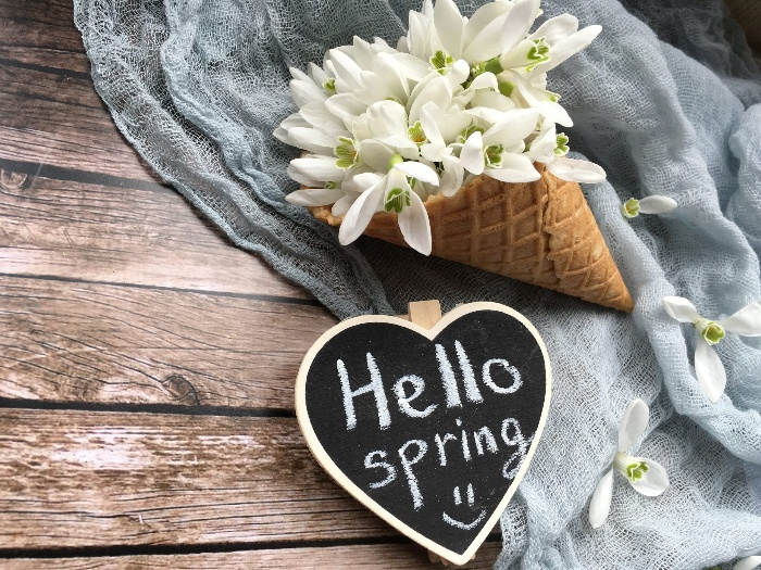 hello spring sign and an ice cream cone with white flowers on a wooden table