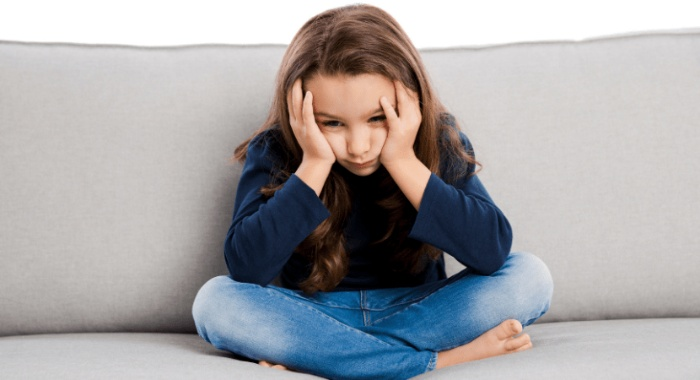 girl sitting in a sofa with her face in her hands looking sad
