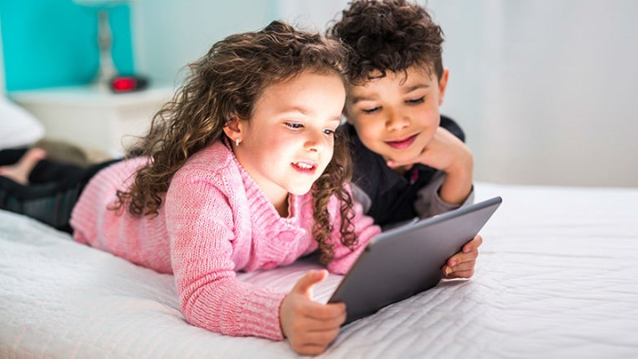 kids screen time little girl and boy laying in bed looking at a tablet