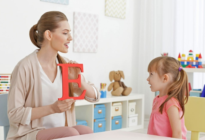 learning with kids mom teaching her little girl the alphabet showing her the letter E
