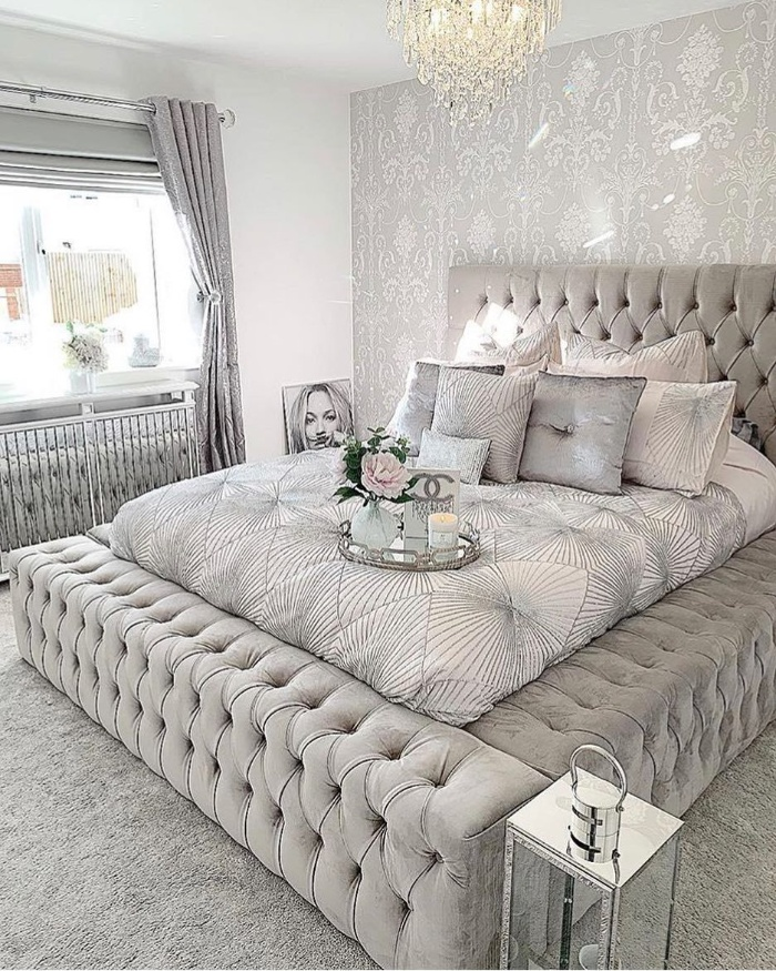 luxury upholstered light gray bed with lots of pillows chandelier light gray bedroom