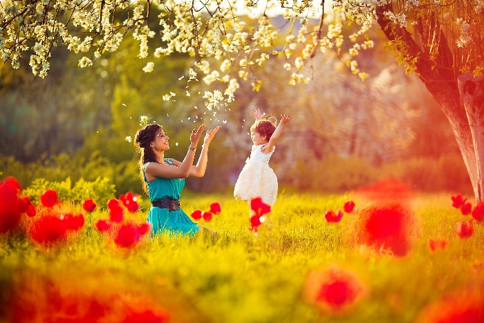 mother and child playing outside under a blossoming tree in the middle of a lawn