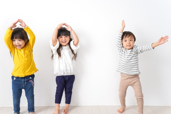 three little children dancing at home and smiling