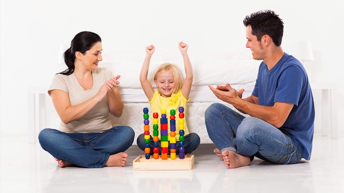 praise kids parents clapping at their child for successfuly arranging colorful toys