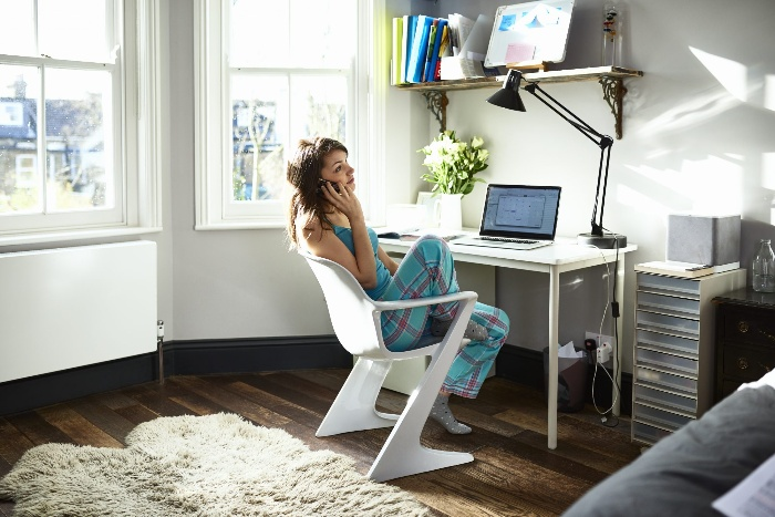 remote work woman sitting on a chair speaking on the phone in a home office