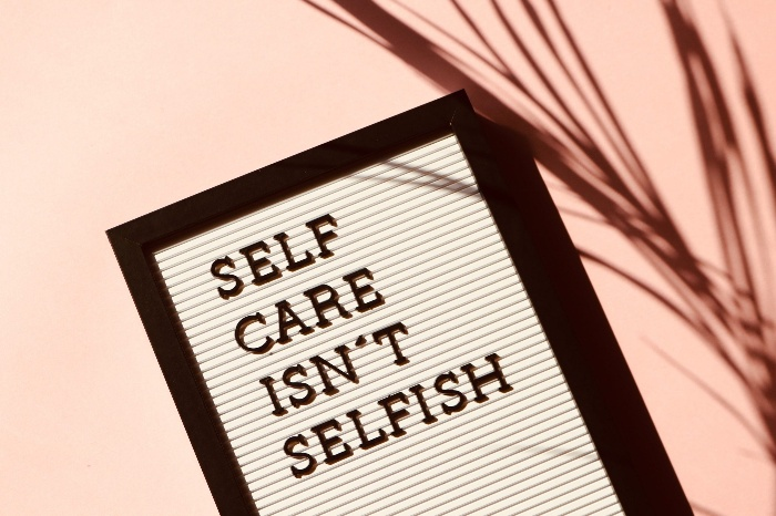 self care isn't selfish writing on a table on a pink table