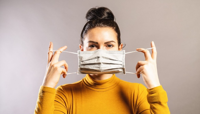 woman with black hair and yellow turtleneck blouse putting mask down