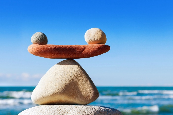 work life balance stones balancing on a beach with the sea in the background