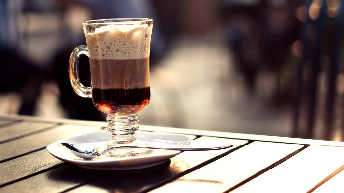 Irish coffee on a wooden table outside in the sun with a plate and spoon