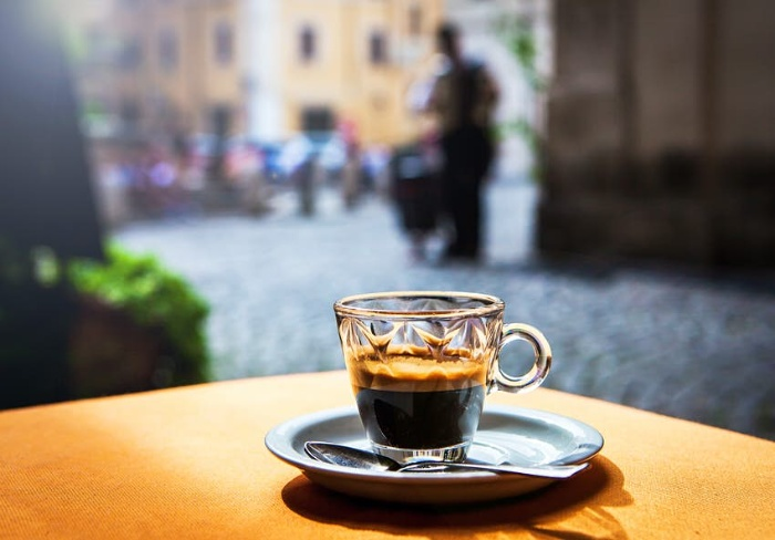 Italian espresso coffee in a glass cup on a table outdoors on the street