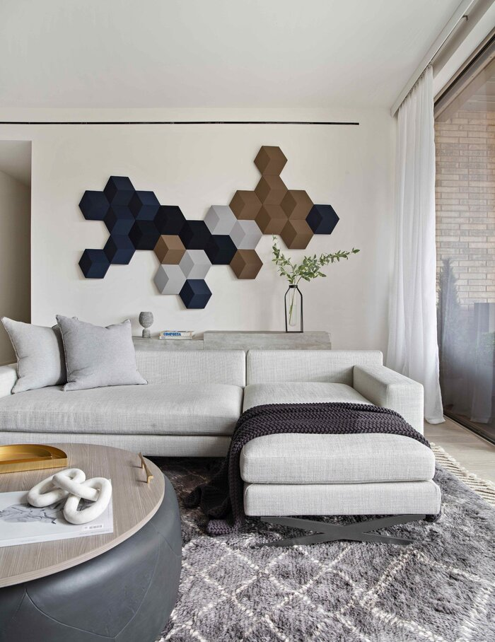 accent wall with colorful pieces in a living room with grey coach
