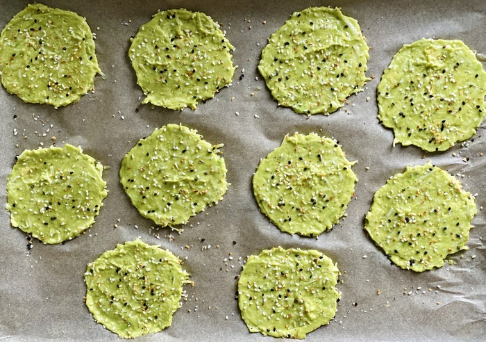 avocado chips on a piece of parchment paper with sesame and other seeds