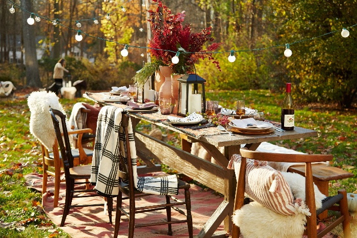 backyard decorating party table with hanging lights and chairs with blankets